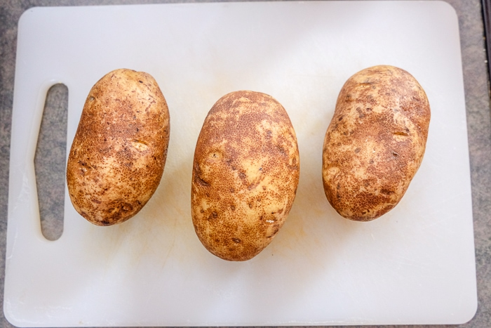 three russet potatoes on white cutting board