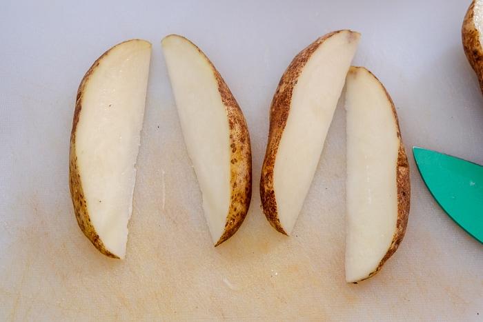 potato wedges cut on white cutting board