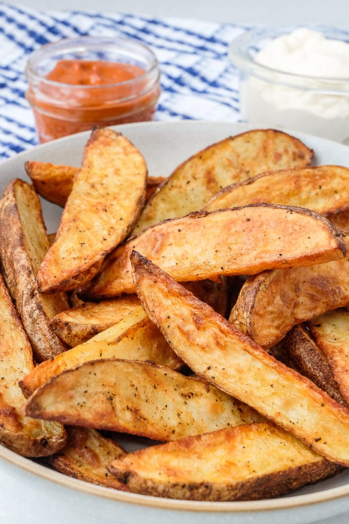 air fryer potato wedges in bowl with dipping sauces behind