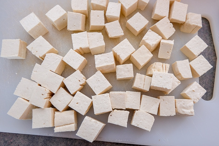 cut and cubed tofu on white cutting board
