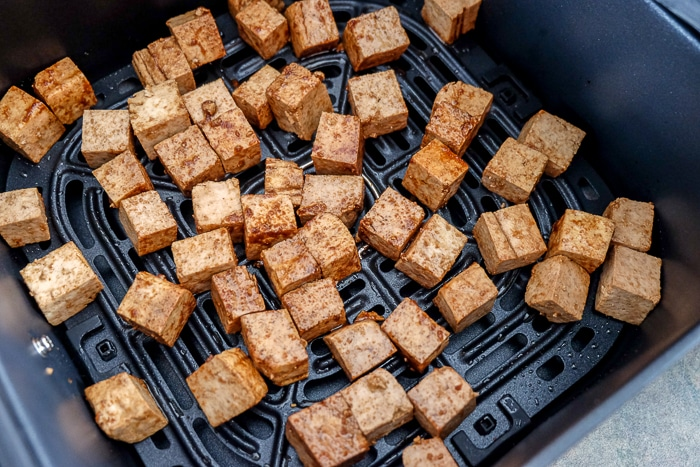 cubes of tofu in black air fryer tray