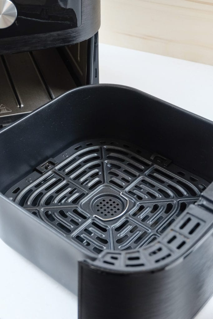 black air fryer with open tray on white counter