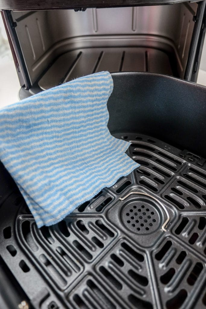 blue cleaning cloth on air fryer tray with air fryer behind