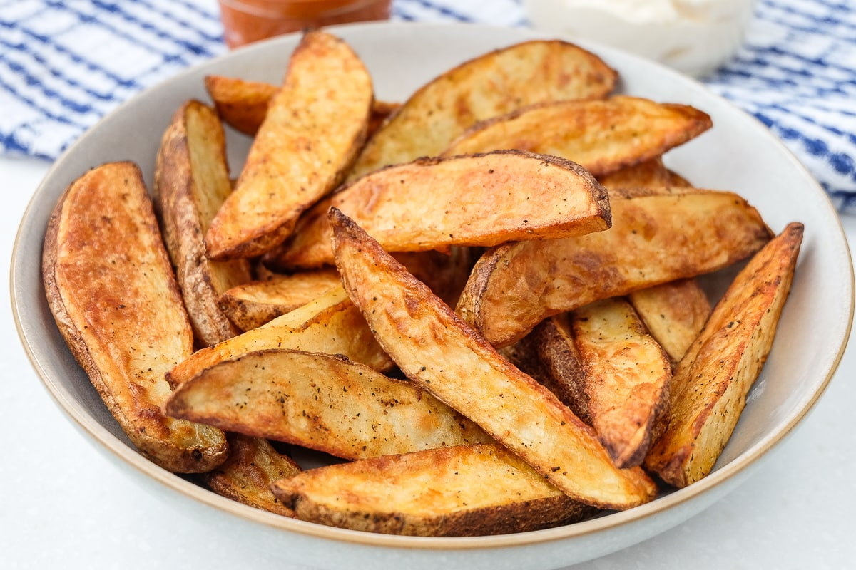 air fryer potato wedges in bowl with dips behind