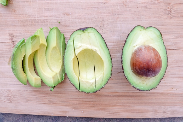 cut up and sliced avocado on a wooden cutting board