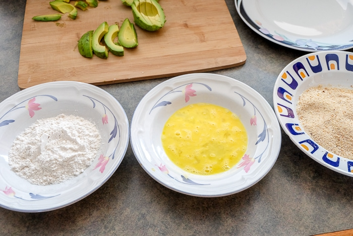 bowls of flour egg and breadcrumbs on counter top with sliced avocado behind