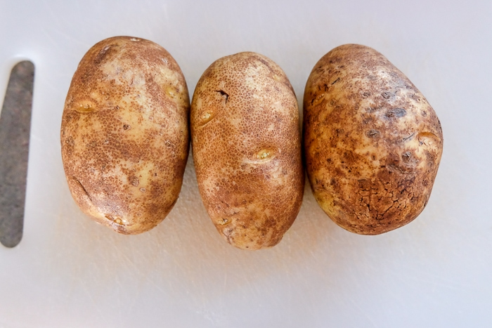 three whole russet potatoes on white cutting board