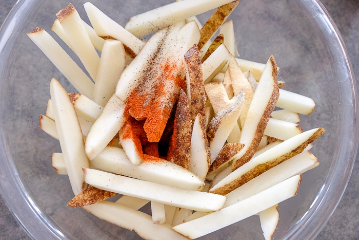 fresh cut fries in bowl with oil and spices on top