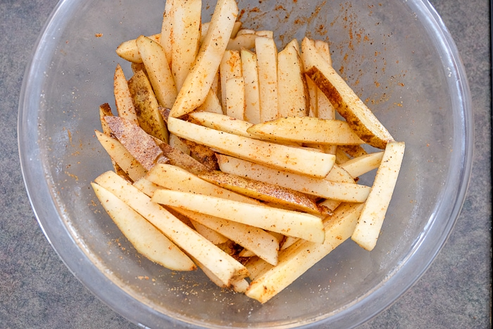 clear glass bowl of fresh cut fries coated in spice and oil