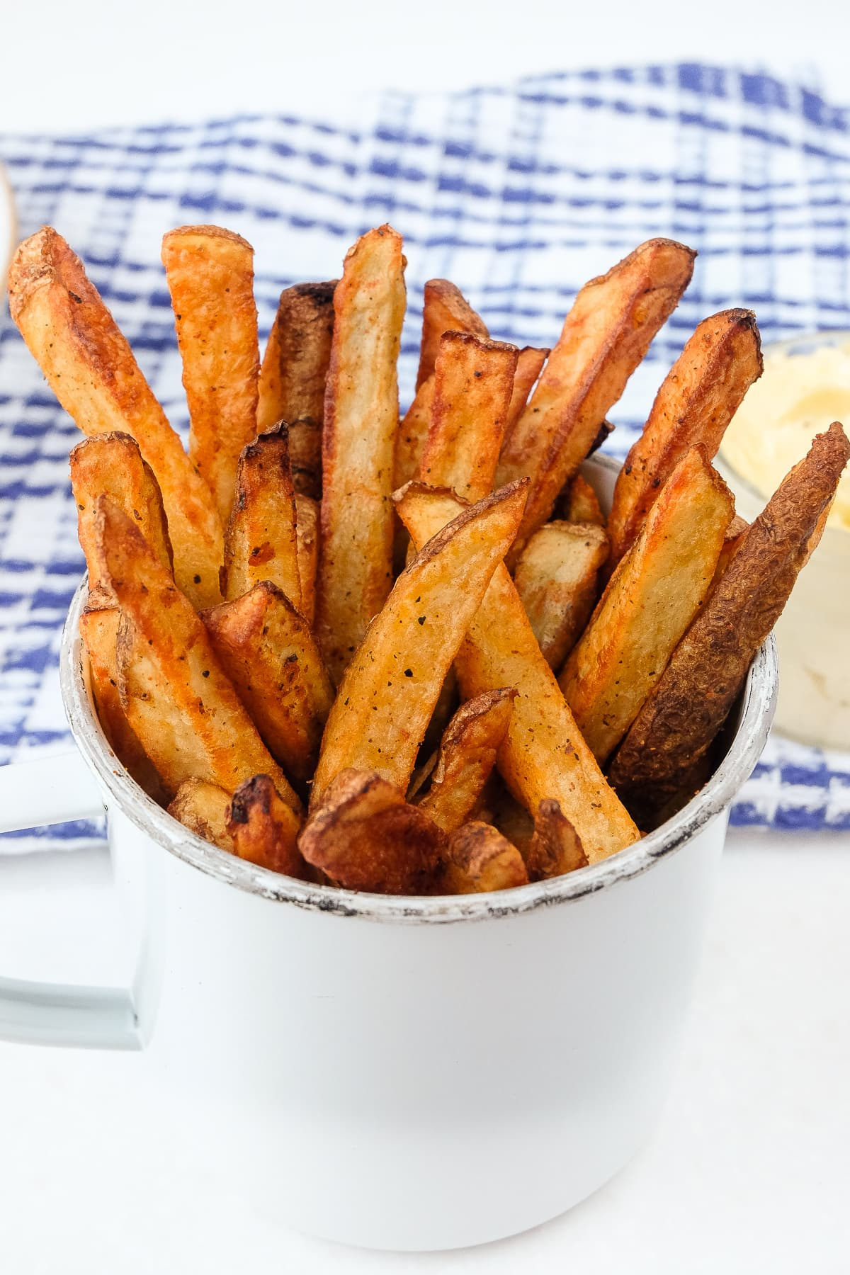 homemade air fryer french fries in cup with mayo behind