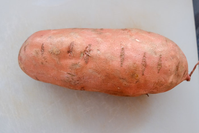 large unpeeled sweet potato on white cutting board