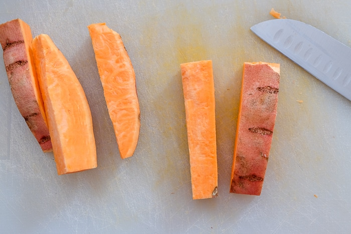 sweet potato fries cut thick on cutting board with knife beside