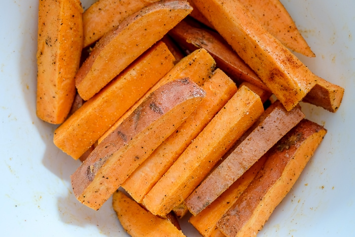 sweet potato fries in white bowl mixed in spices and oil
