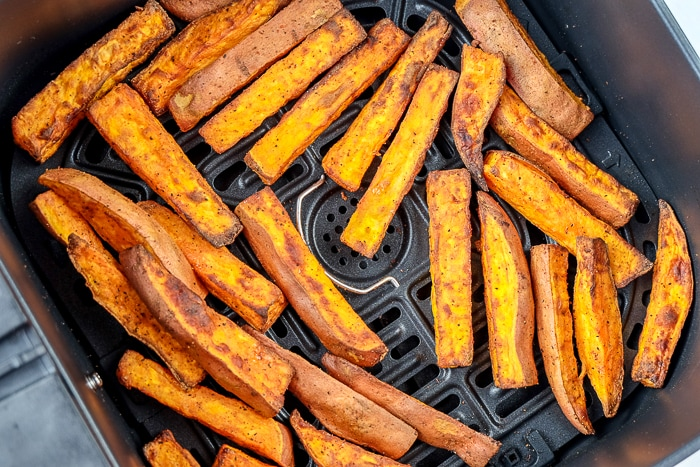 cooked sweet potato fries on black air fryer tray
