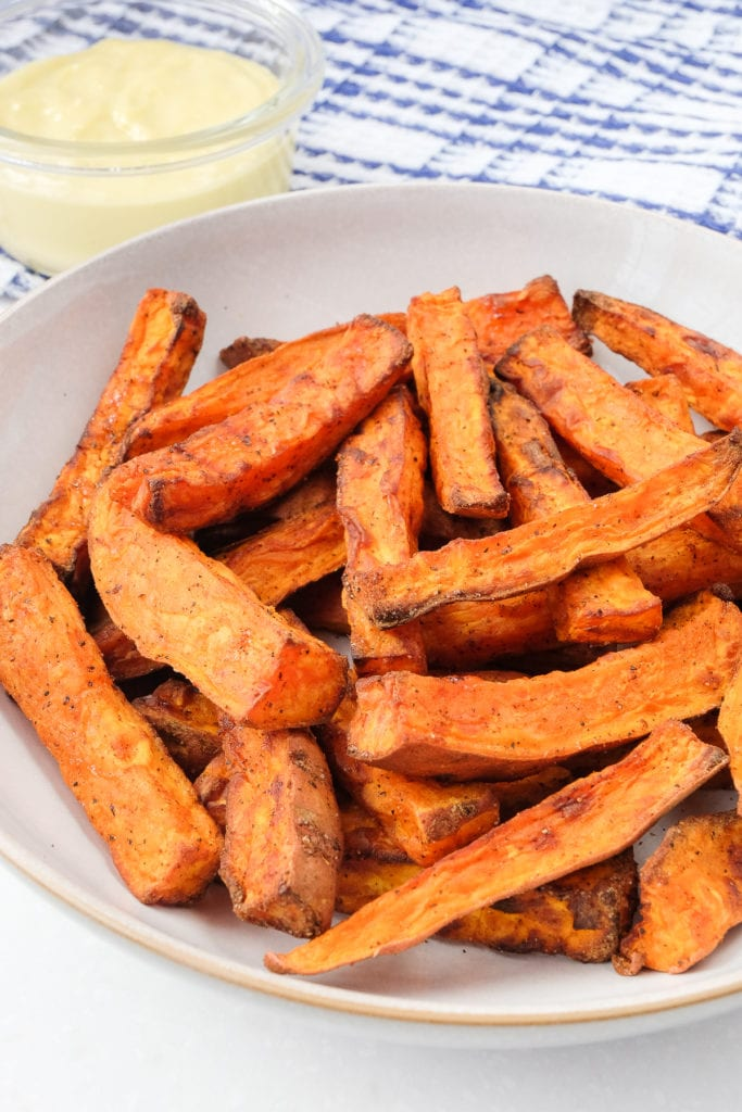 air fryer sweet potato fries in bowl with mayo behind