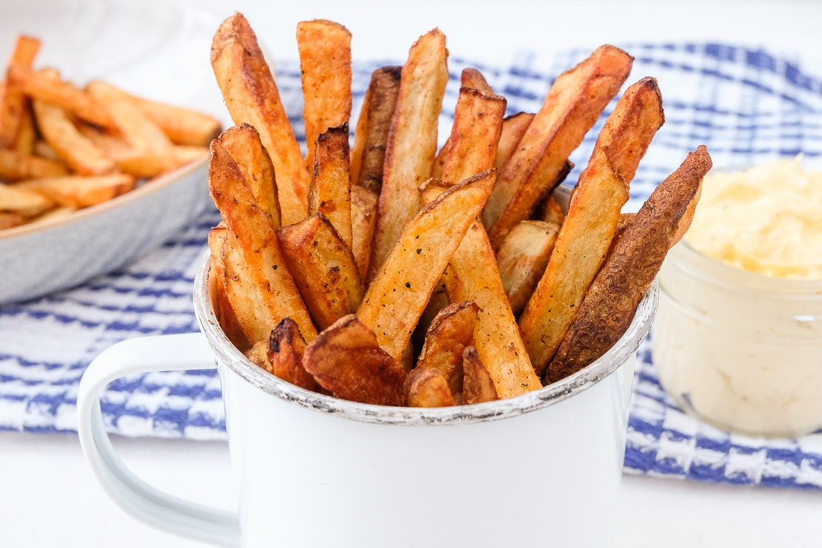 air fried french fries in cup with sauce behind