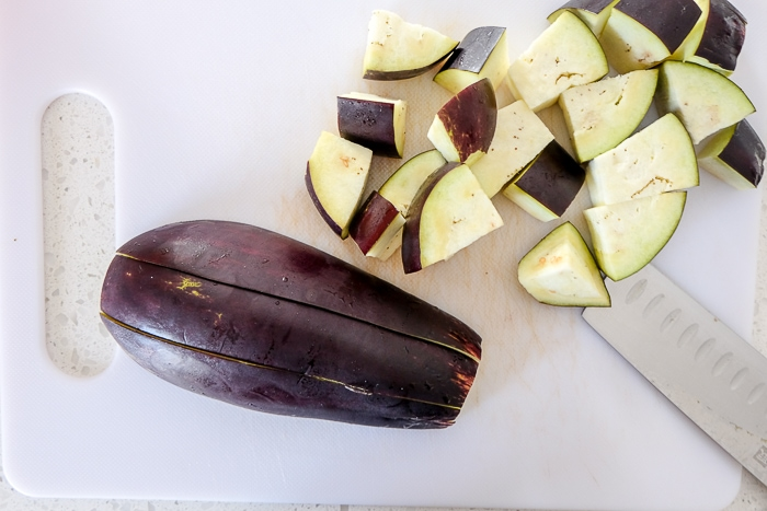 raw eggplant cut into pieces on white cutting board