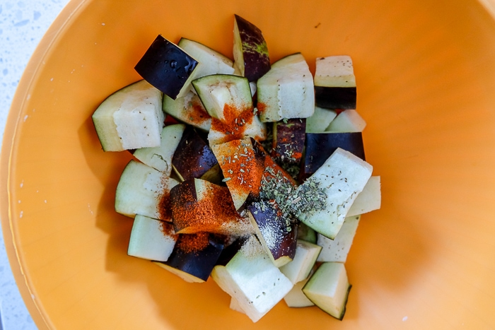 raw eggplant in orange bowl with spices on top
