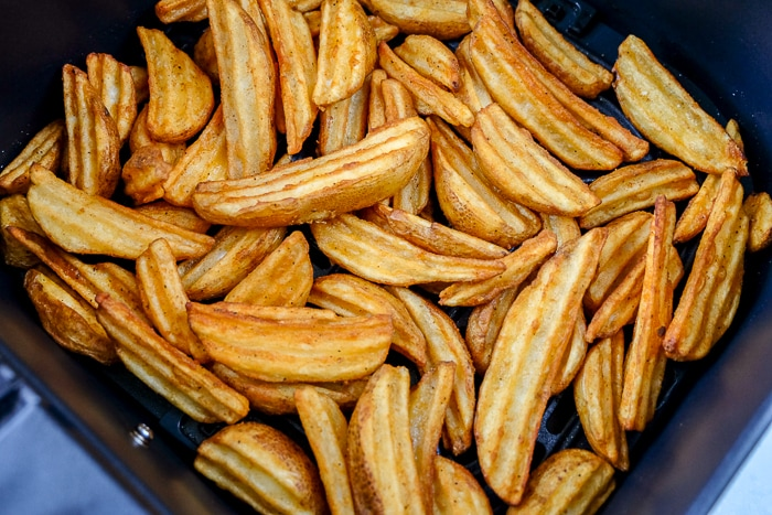 cooked potato wedges in black air fryer tray