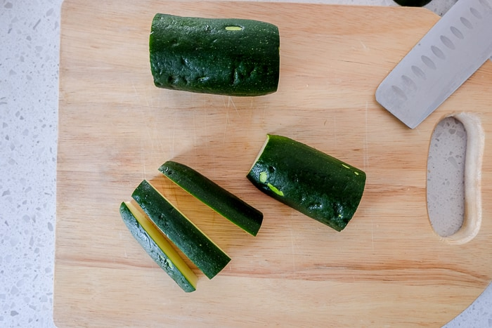 cut zucchini on wooden cutting board with knife beside