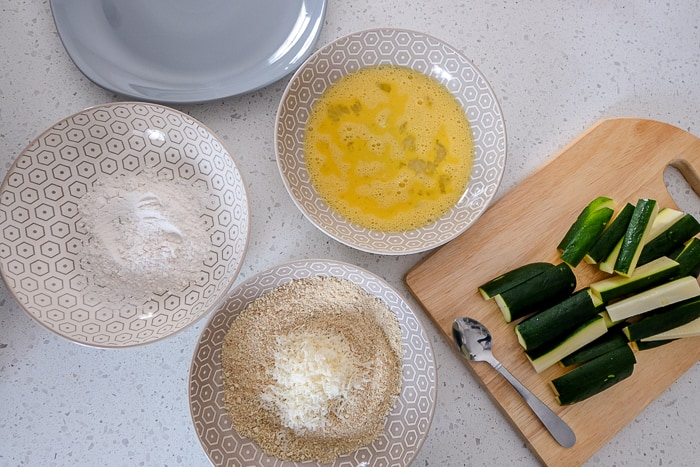 plate with egg breadcrumbs and flour on counter top beside cut zucchini sticks