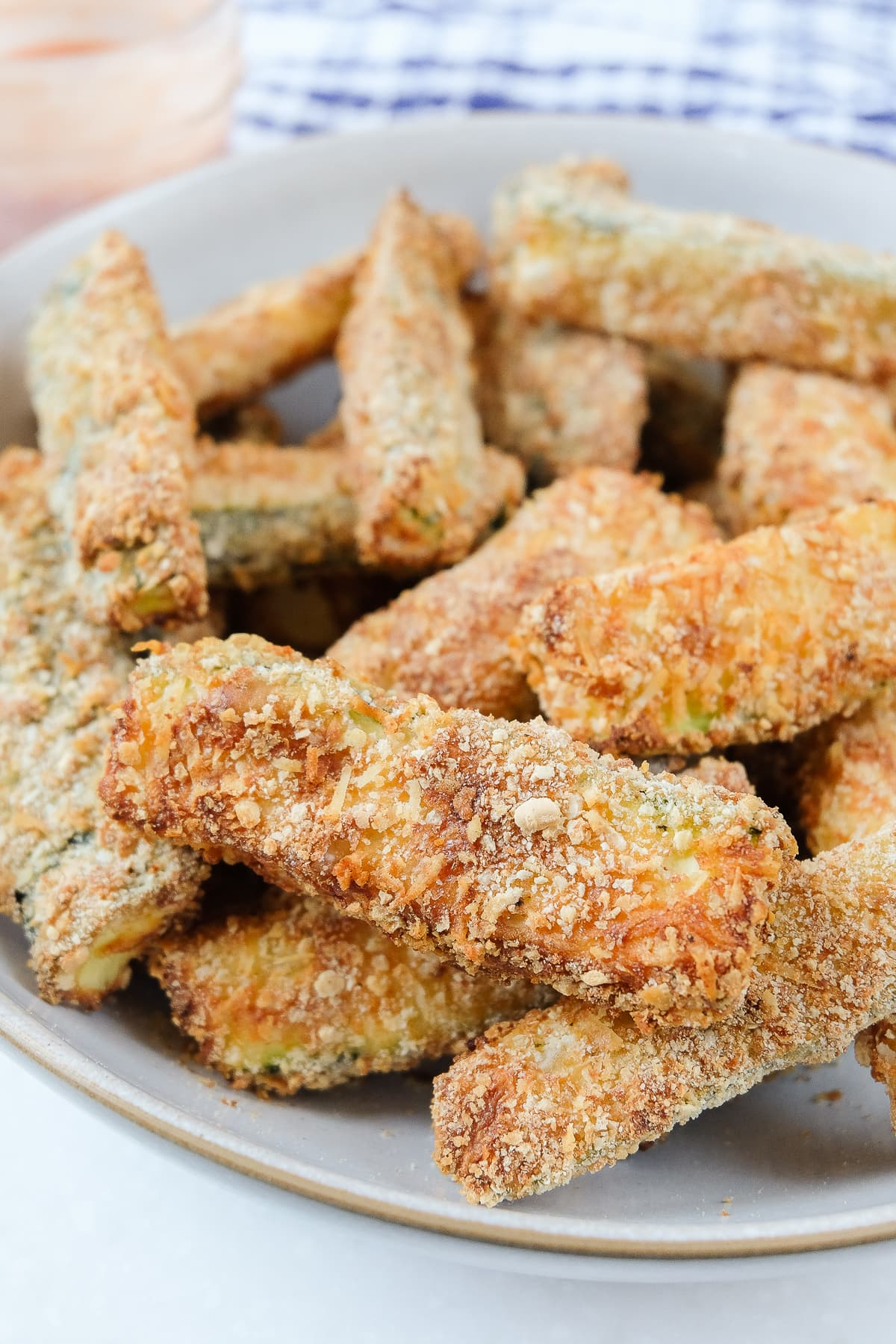 crispy air fried zucchini fries in bowl with sauce behind