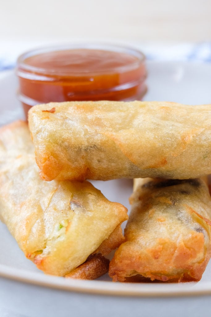 crispy spring rolls in bowl with dipping sauce behind