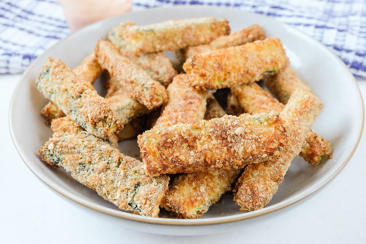 breaded zucchini fries in bowl with towel behind