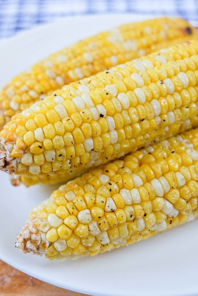 cooked corn on the cob on white plate with blue cloth behind