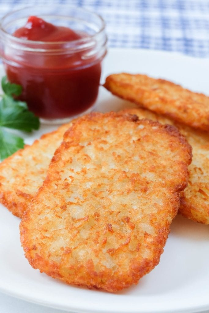 crispy golden brown hash brown patties on white plate with ketchup behind