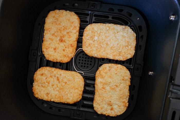 four frozen hash brown patties in black air fryer tray