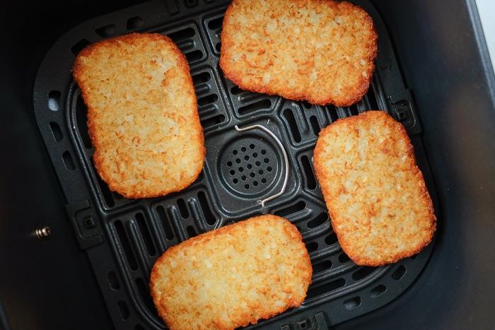 golden brown hash brown patties in black air fryer tray