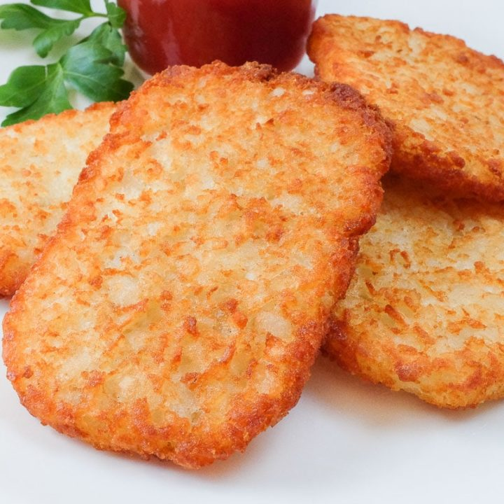 crispy air fried hashbrowns on plate with ketchup behind