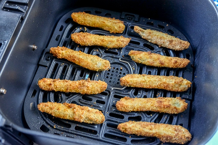 cooked breaded pickles in black air fryer tray