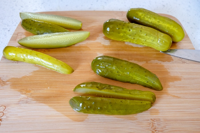 pickle spears cut on wooden board on counter top