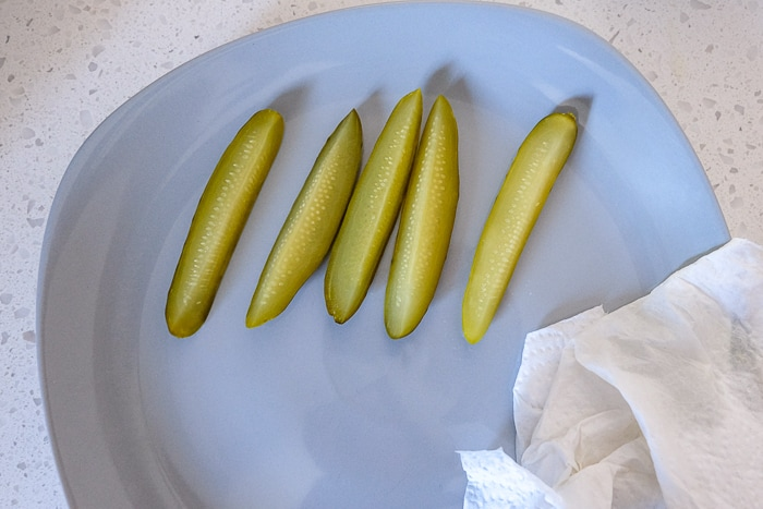 cut pickle spears on blue plate with paper towel beside
