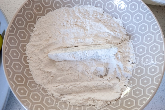pickle spear coated in flour in bowl