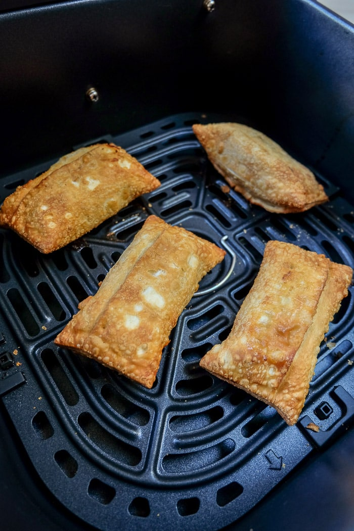 cooked egg rolls in a black air fryer tray