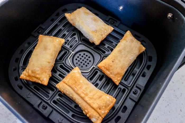 frozen egg rolls in a black air fryer tray