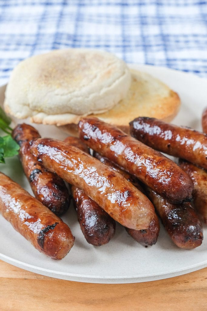 breakfast sausages on plate with toasted english muffin behind