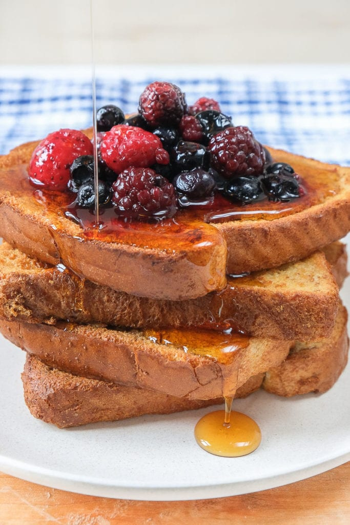 air fried french toast in a stack on plate with berries and syrup on top