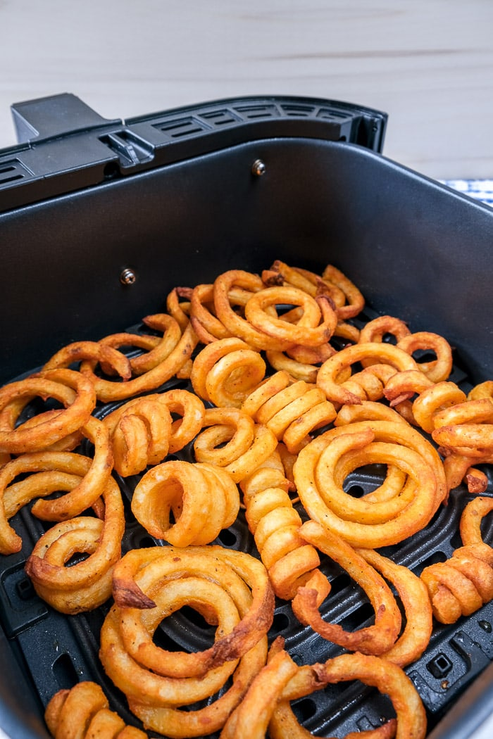 cooked curly fries in air fryer tray