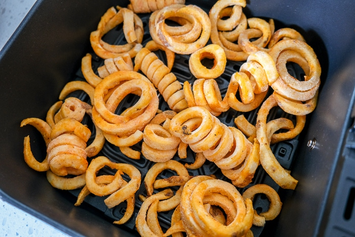frozen curly fries in black air fryer tray on counter