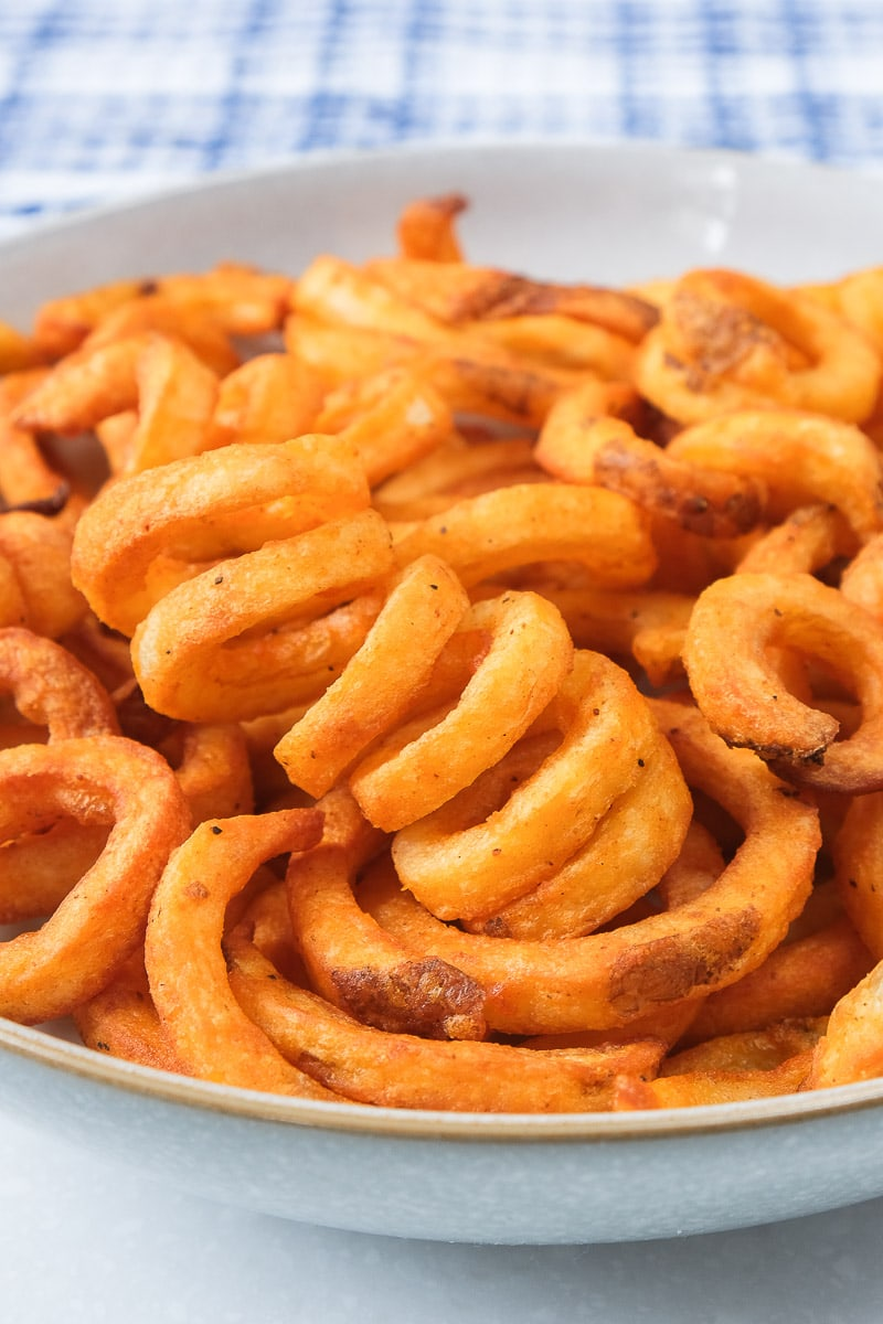 crispy orange curly fries in a bowl with blue towel behind