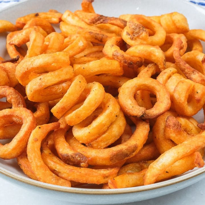 crispy curly fries in bowl on counter top