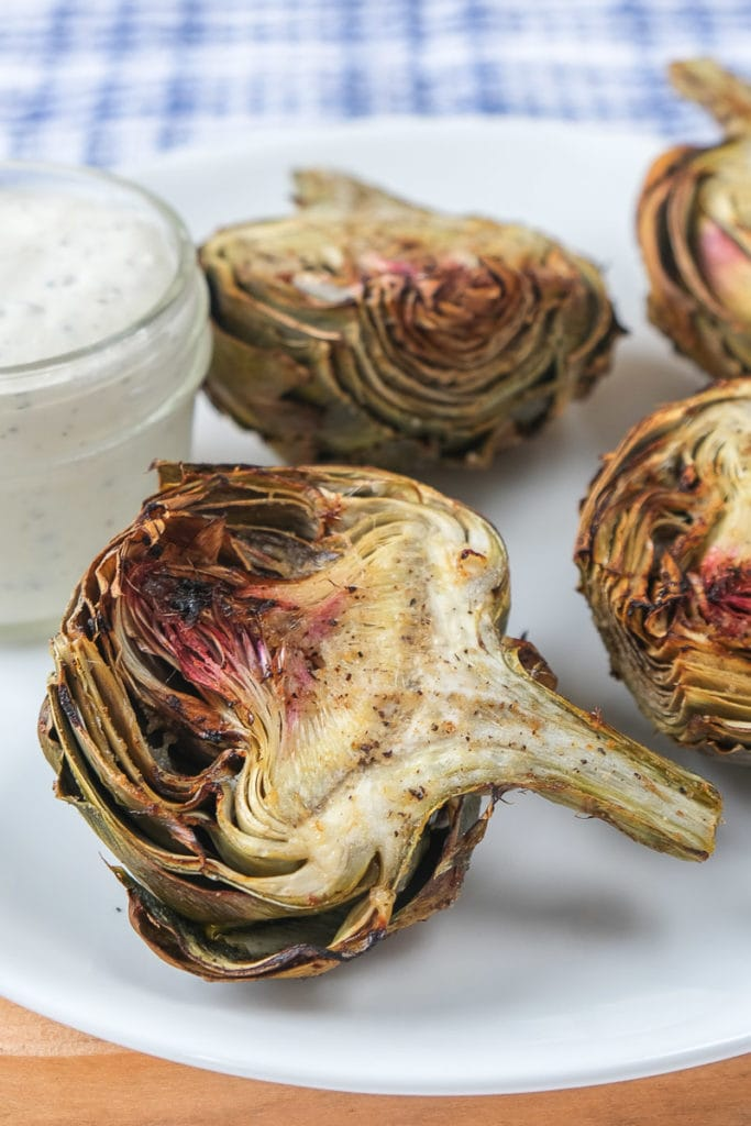 cooked artichokes on white plate with dip beside