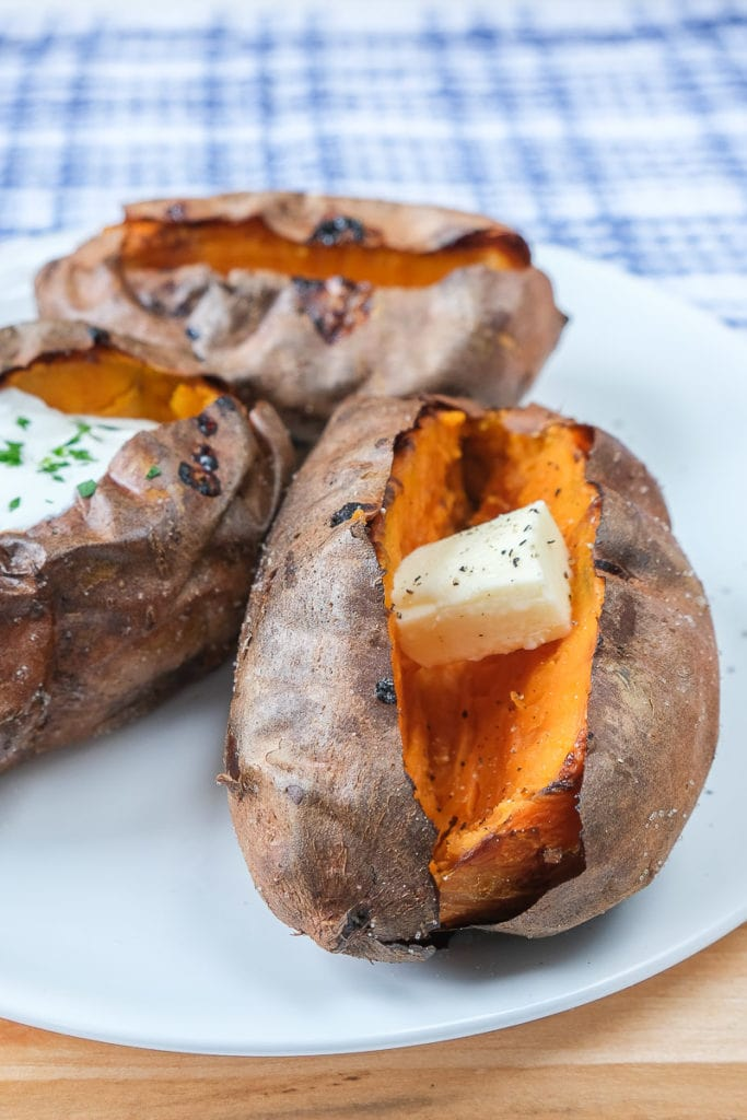 baked sweet potatoes on white plate with butter inside