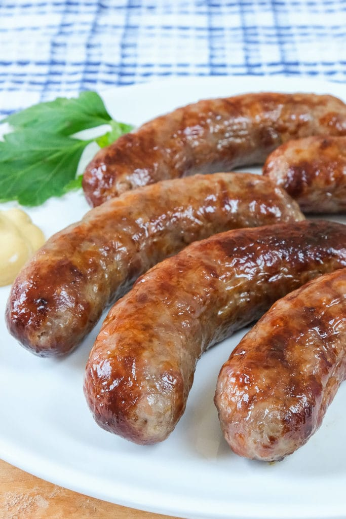 crispy brats on white plate with mustard and parsley beside