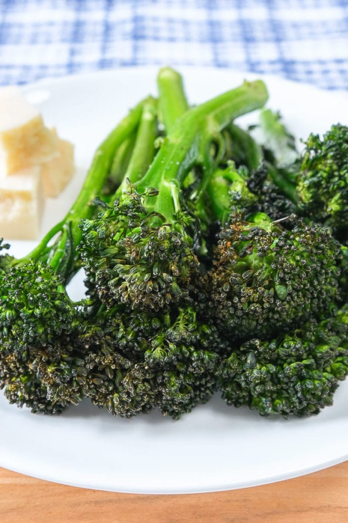 green broccolini on white plate with wooden board underneath