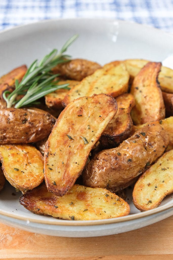 crispy fingerling potatoes with rosemary in bowl on wooden board